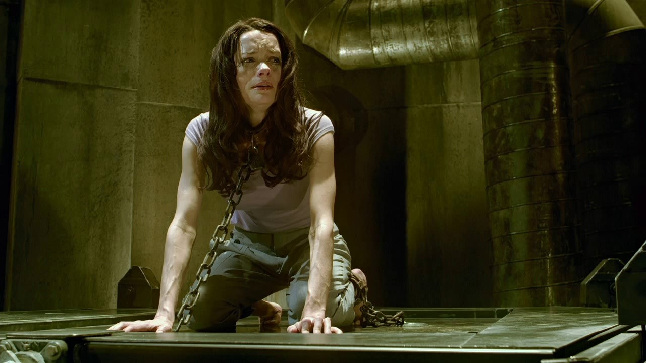 Shawnee Smith as Amanda Young in Saw. Amanda is in a darkened concrete room with metal piping. She is on all fours on the floor, her movement restricted by heavy chairs around her neck and ankle. Her expression is fearful.